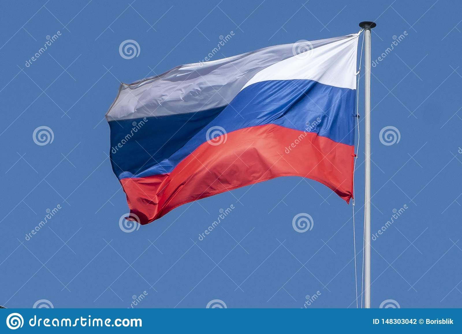 Flag of Russia, the Russian Federation, the tricolor against the blue sky develops in the wind