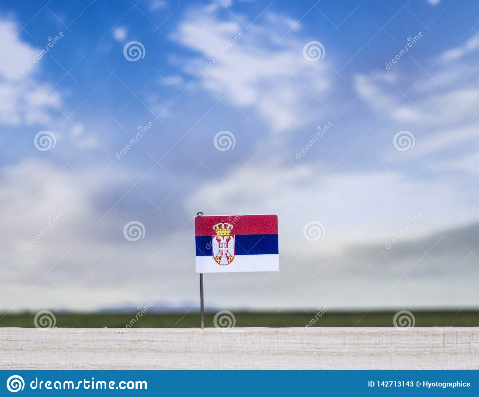Flag of Serbia with vast meadow and blue sky behind it.