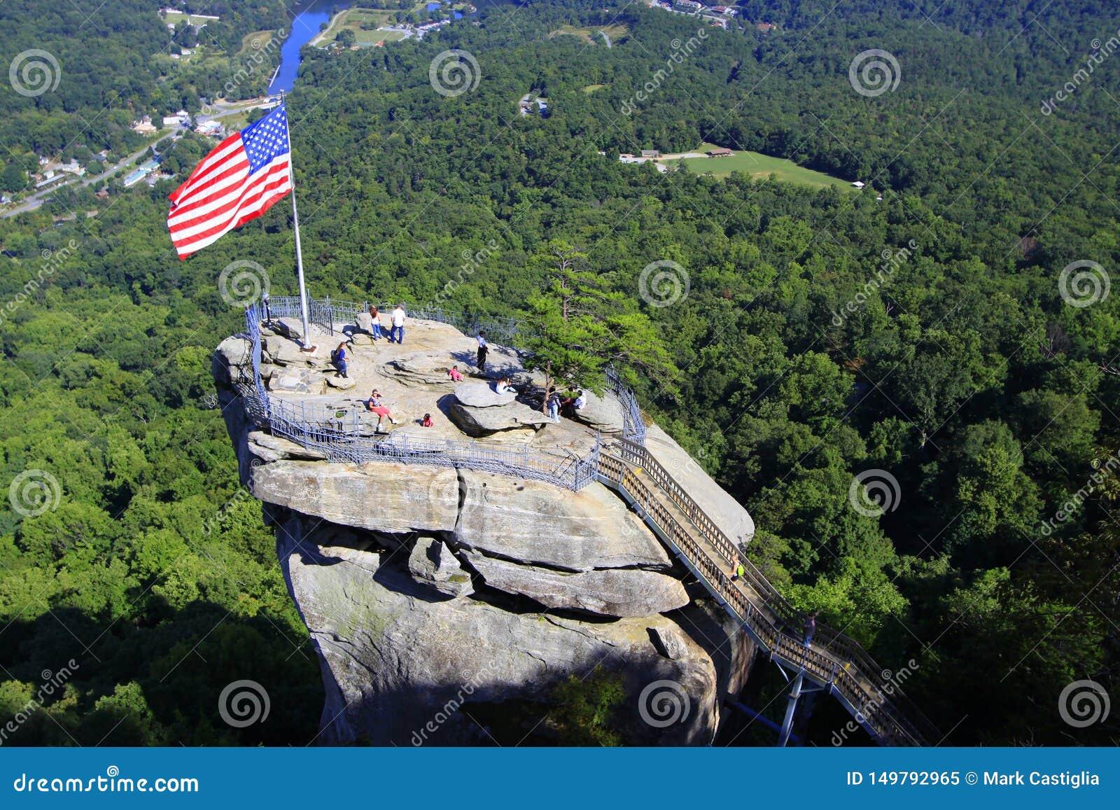 Flaga amerykańska i turyści przy kominem Kołysamy w Pólnocna Karolina, usa