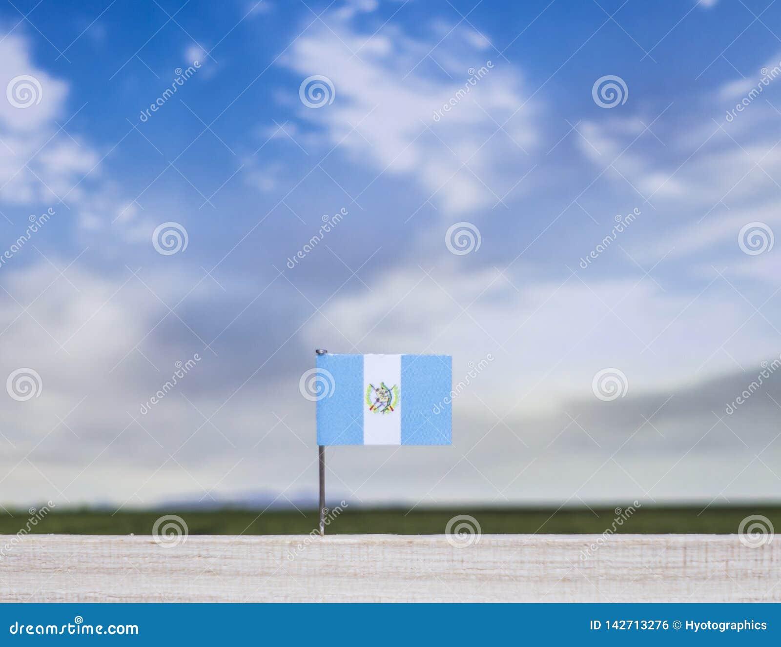 Flaga Gwatemala z szeroką łąką i niebieskim niebem za nim