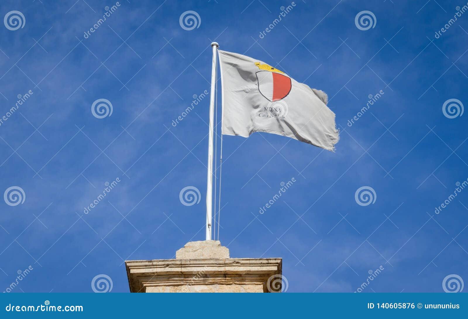 Flaga Mdina miasta cios w wiatrowym popióle nad Medina brama w Środkowym Malta na starym dziejowym kasztelu