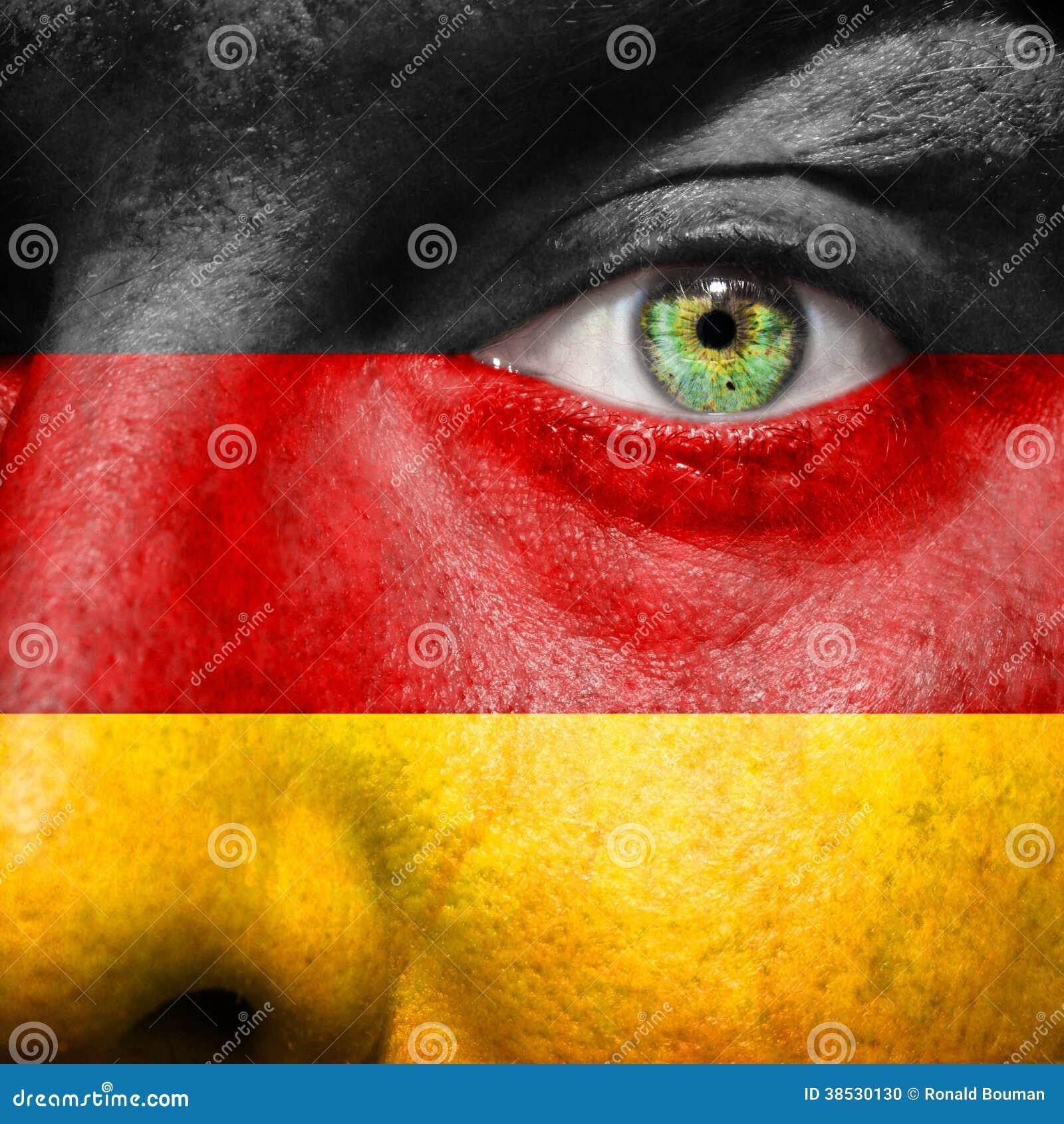 Flagge gemalt auf Gesicht mit grünem Auge, um Deutschland-Unterstützung zu zeigen
