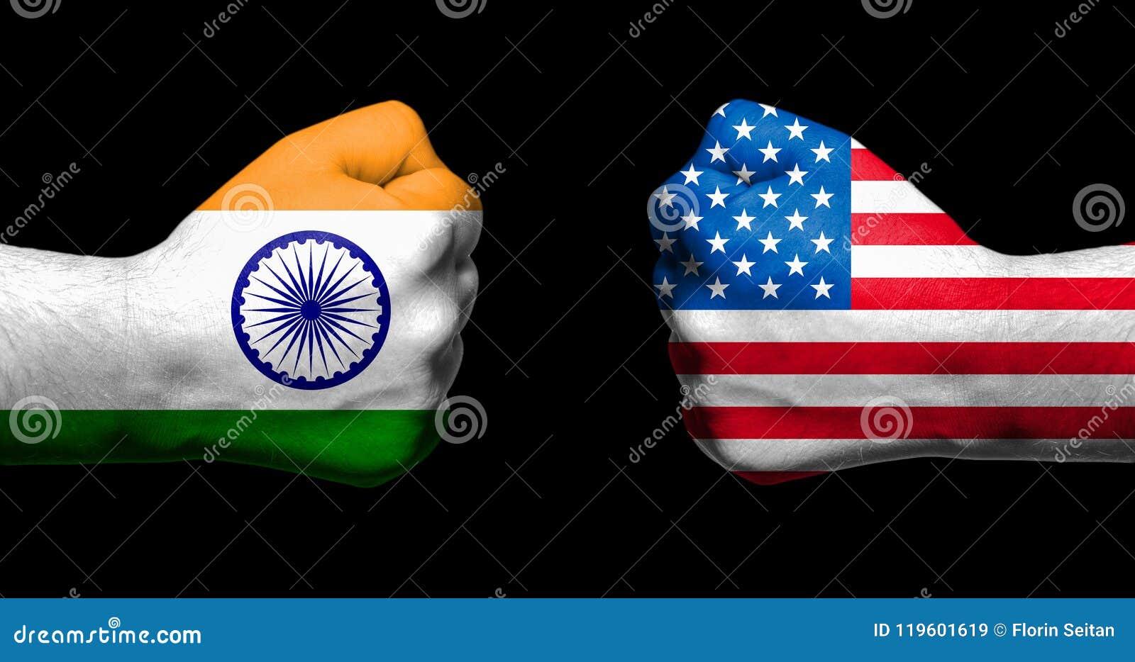 Flaggen von Indien und von Vereinigten Staaten gemalt auf zwei geballten Fäusten, die auf schwarzem Hintergrund-/Tarifkonflikt c