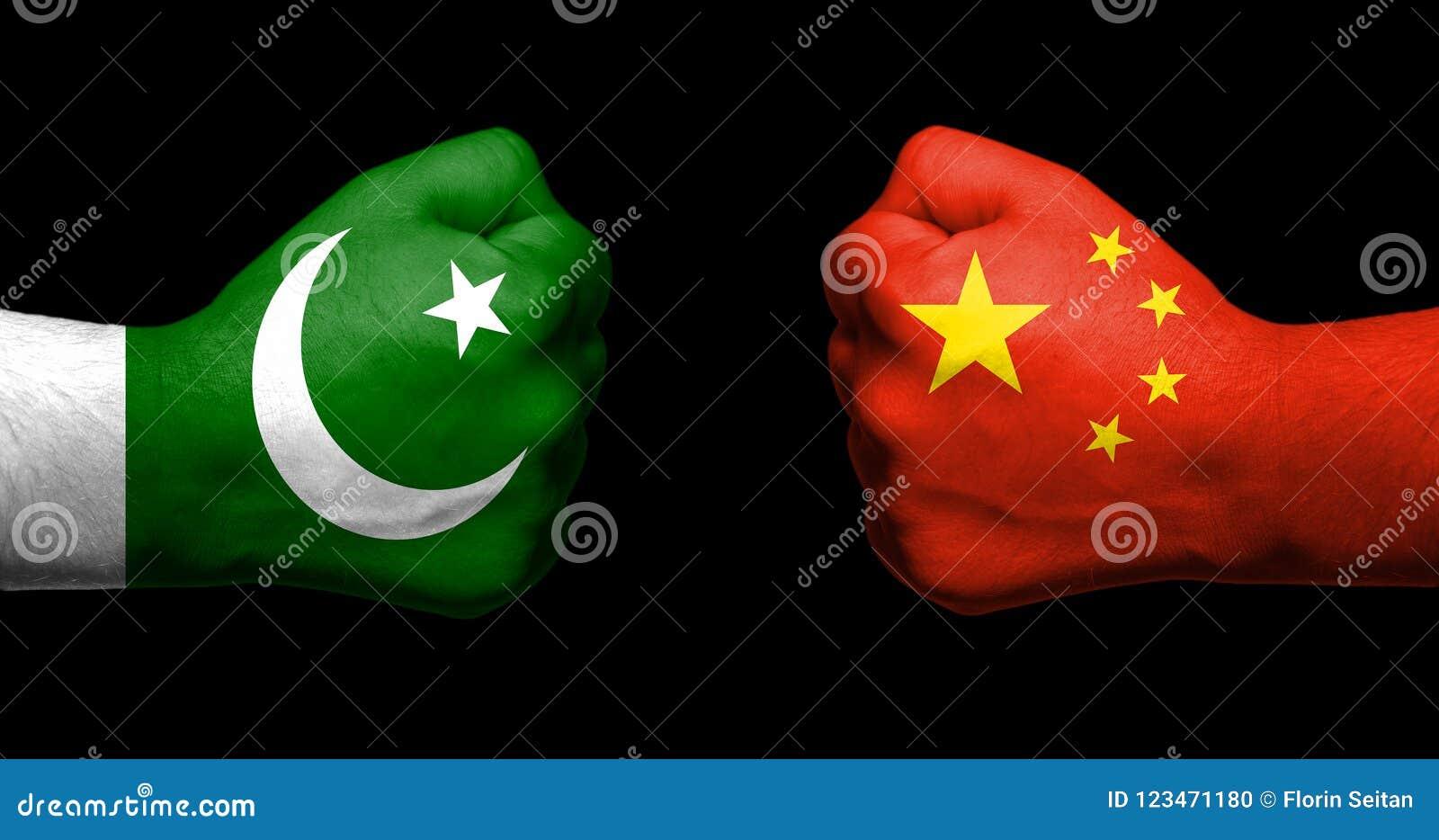 Flaggen von Pakistan und von China gemalt auf dem Gegenüberstellen zwei geballter Fäuste