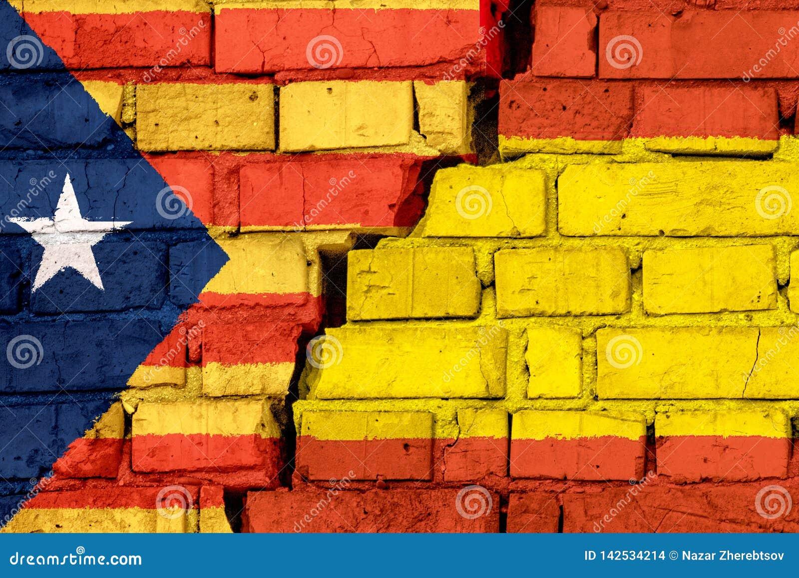 Flaggor av Catalan och Spanien på tegelstenväggen med den stora sprickan i mitt Symbol av problem mellan länder