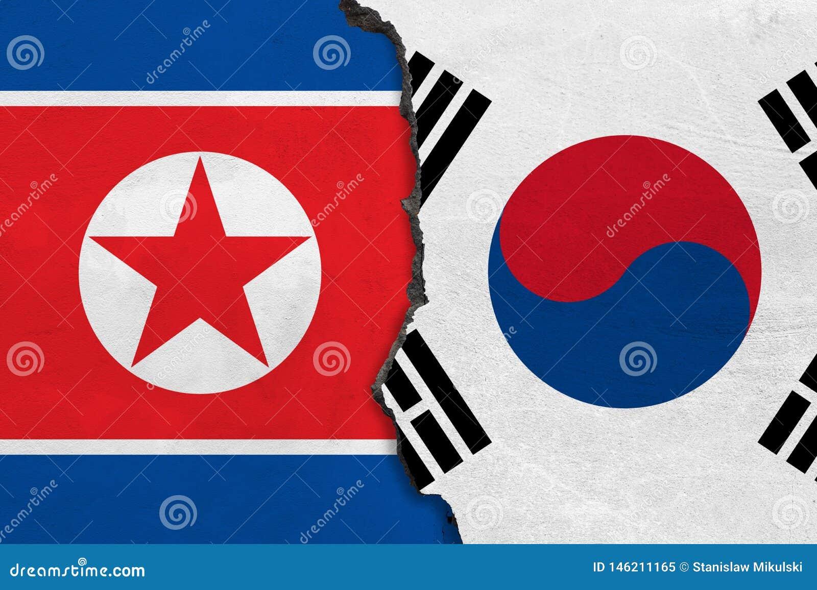 Flaggor av Nordkorea och Sydkorea som målas på den spruckna väggen