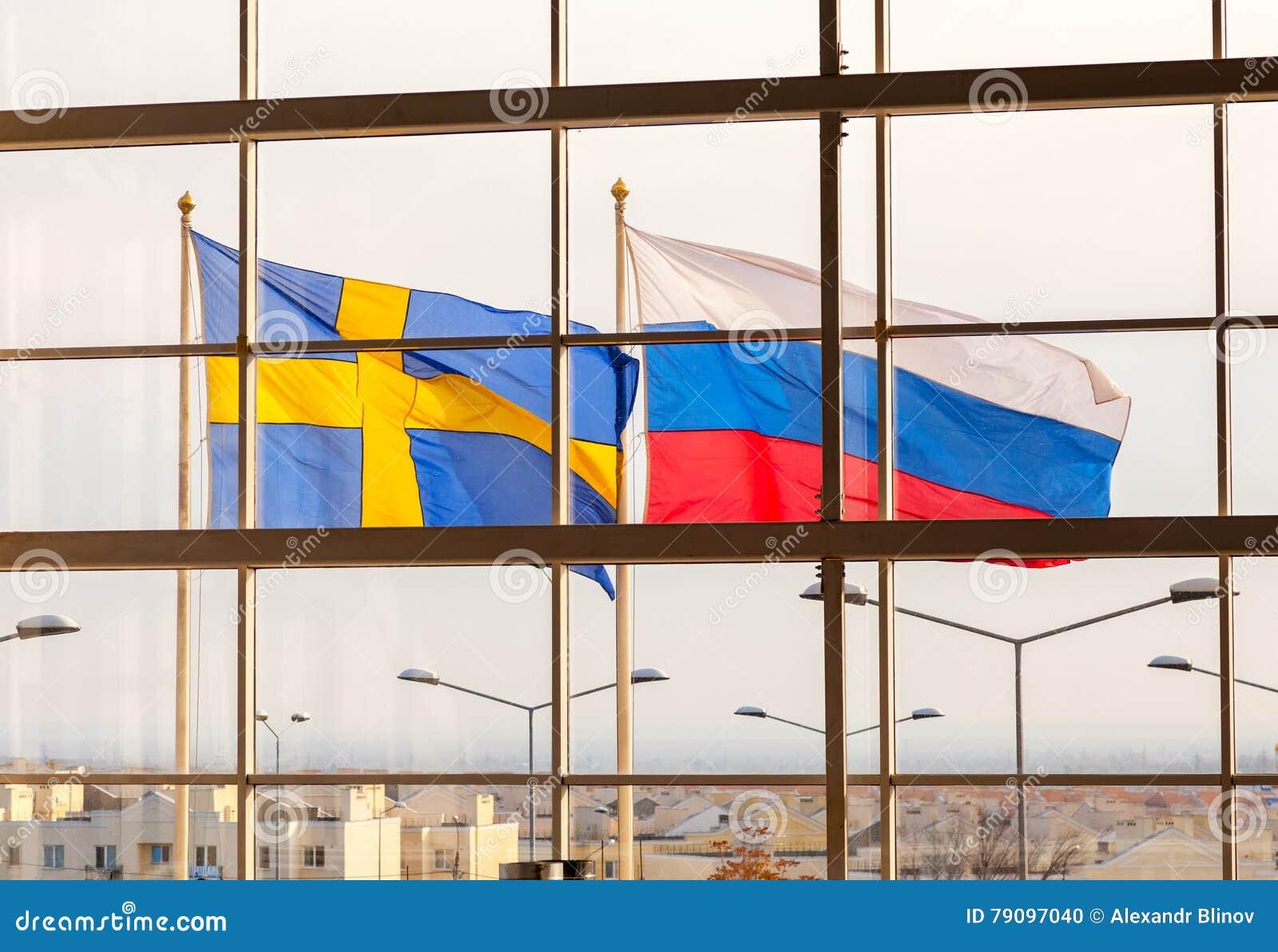 Flaggor av Sverige och Ryssland som vinkar mot fönster