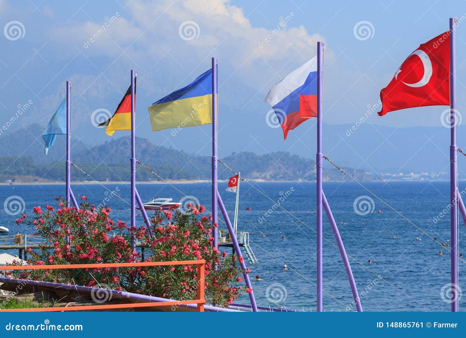 Flaggor av Turkiet, Ryssland, Ukraina, Tyskland och Kasakhstan p? stranden i Kemer
