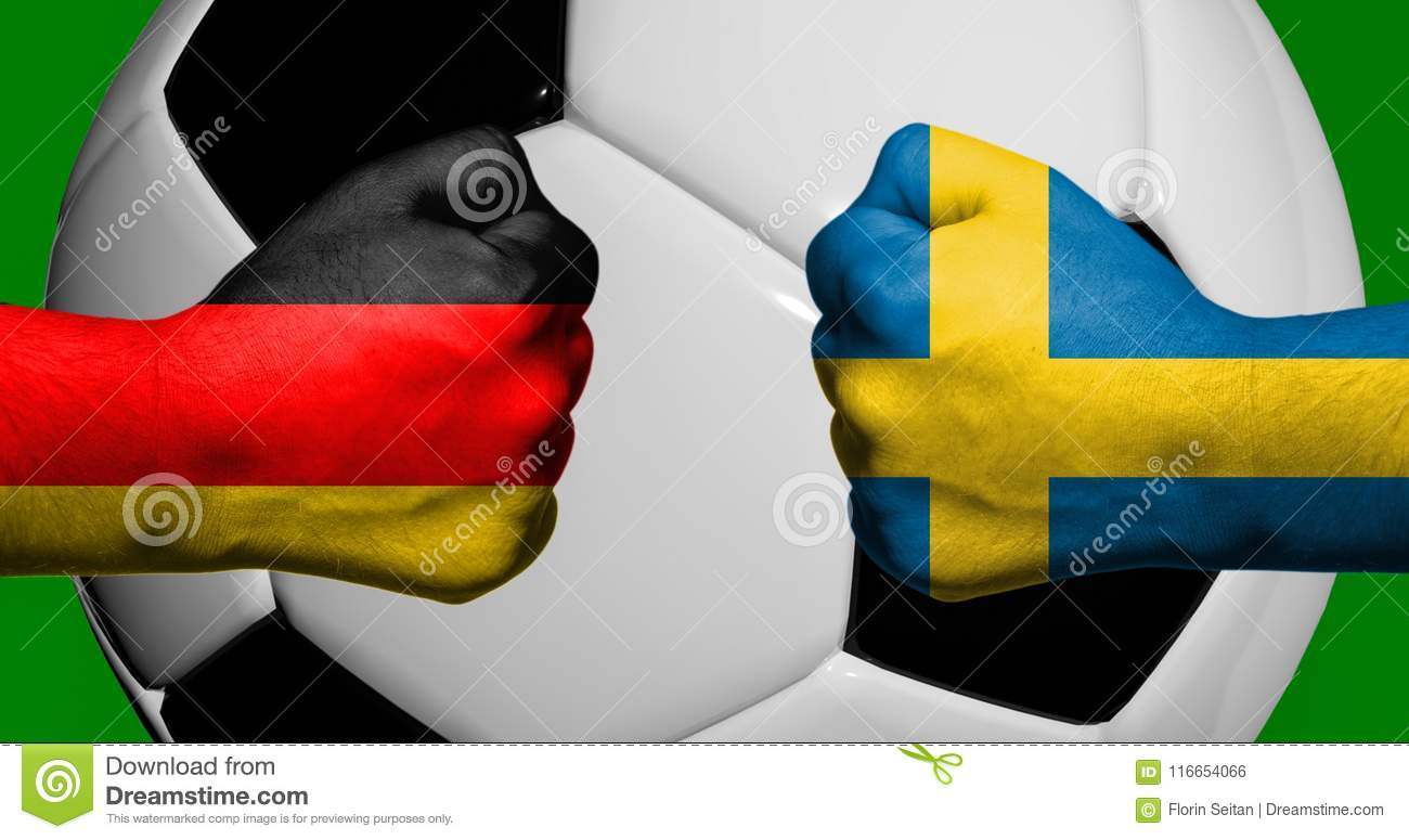 Flags of Germany and Sweden painted on two clenched fists facing each other with closeup 3d soccer ball in the background/Soccer m