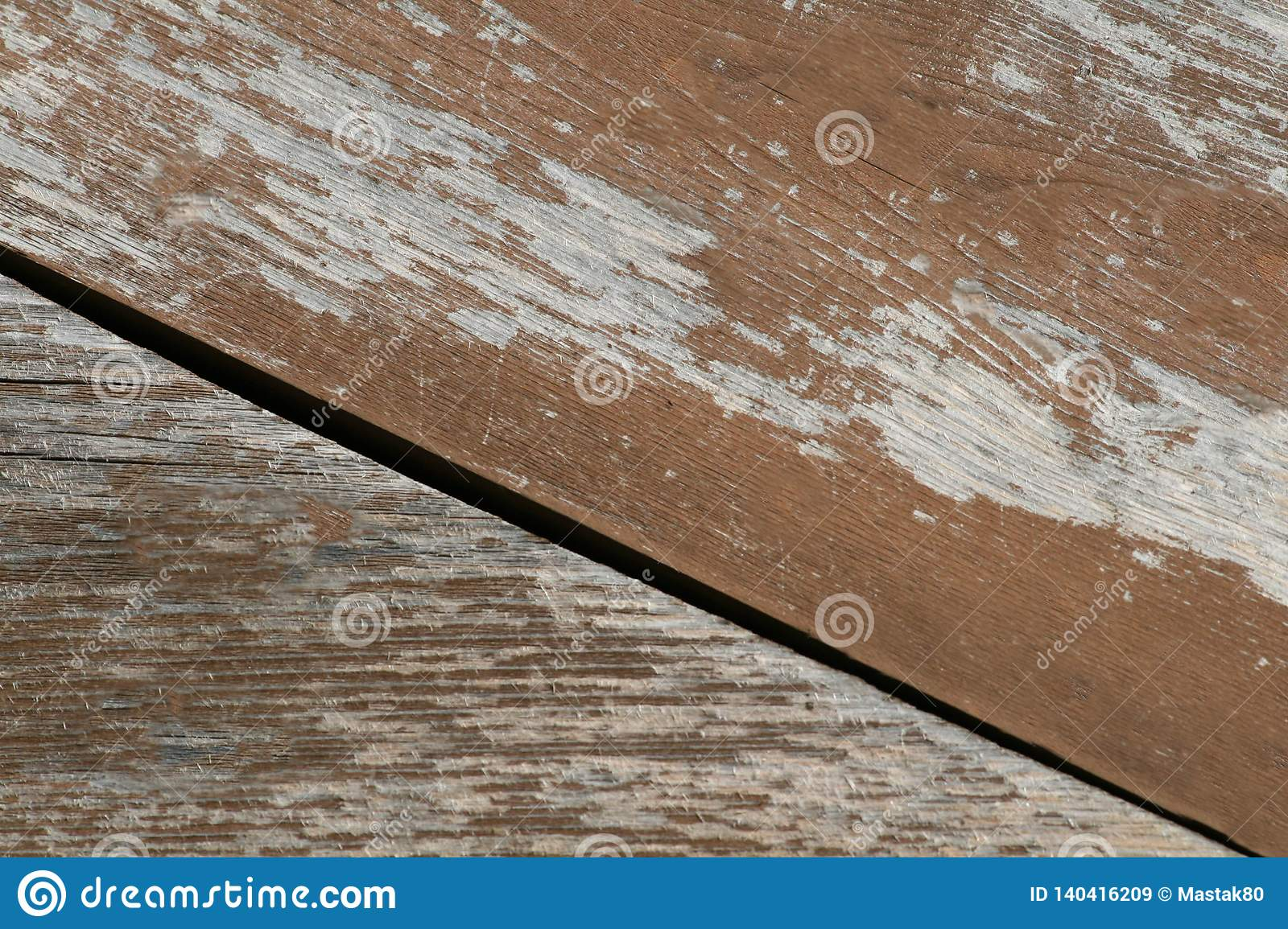 Flaky brown paint on the old wooden surface of the Board