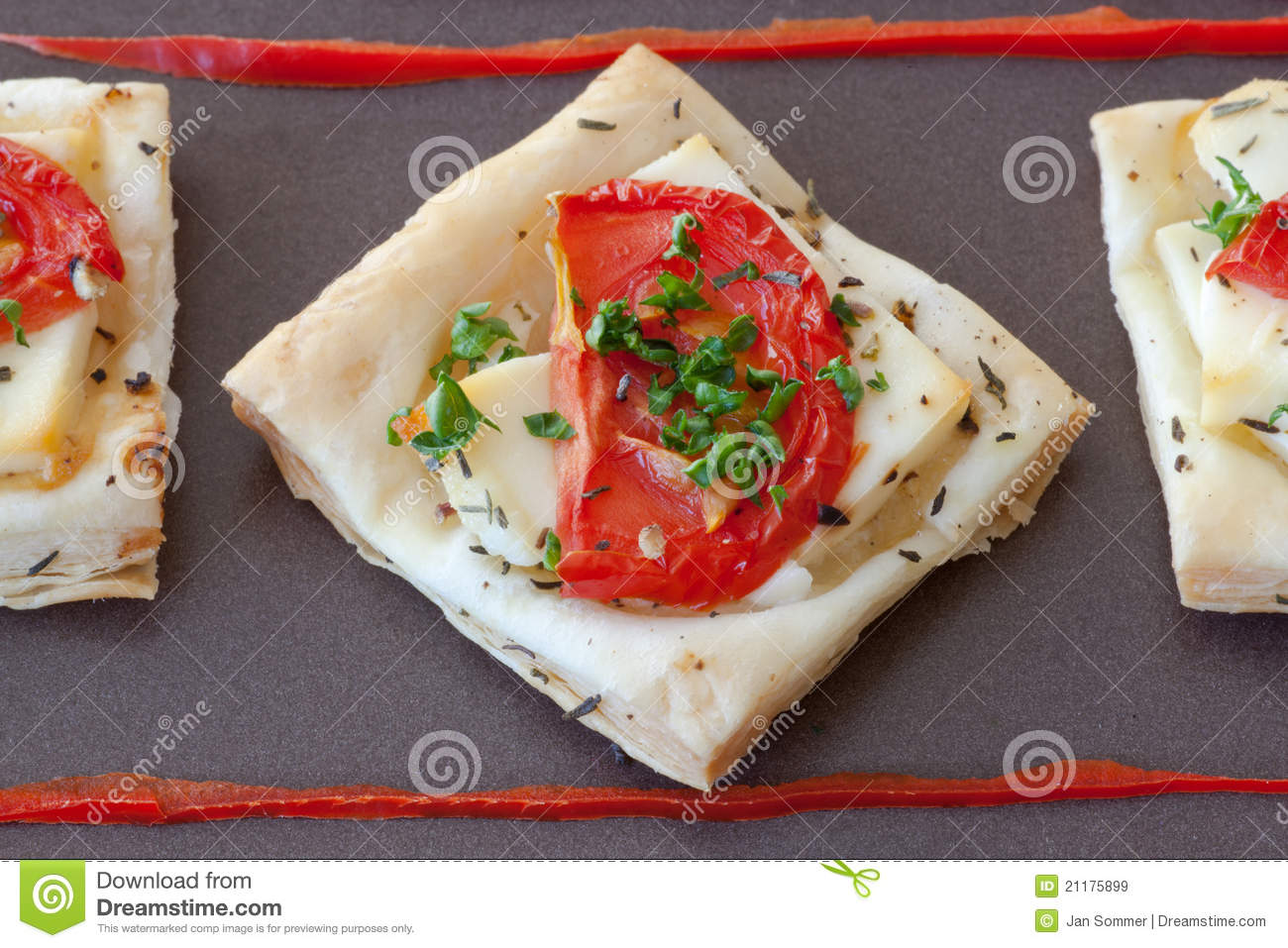 Flaky pastry snack with feta, tomatoes and herbs