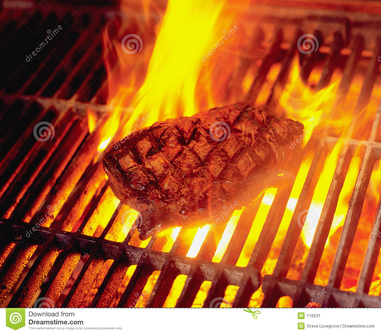 Steak cooking on wood fired flame grill in Restaurant.