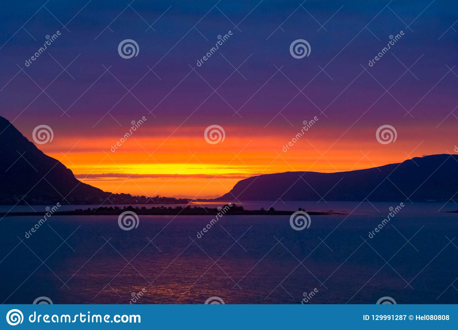 Colorful midsummer sky in orange, yellow and violet at Norwegian Sea, North Norway, Flaming sunset.