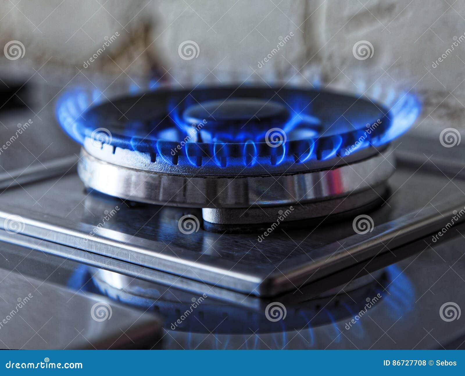 Flammen des blauen Gases Schließen Sie herauf brennenden Feuerring von einem Küchengasherd Abgetöntes Foto