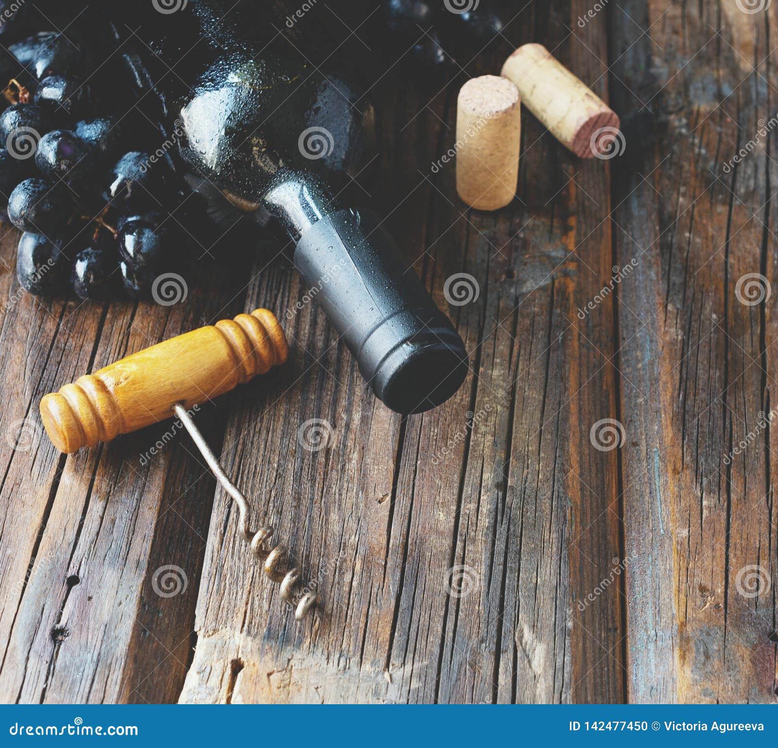 Flasche Rotwein mit frischer Traube und Bündel Korken auf Holztisch