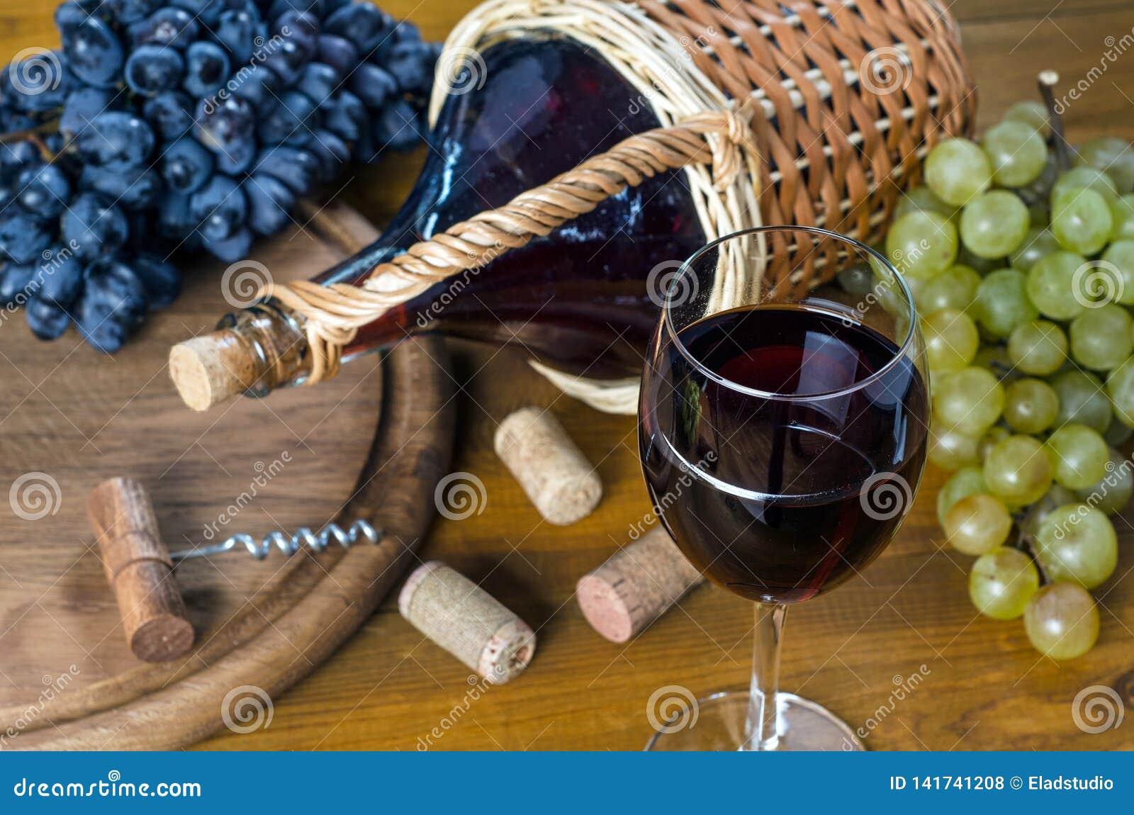 Flasche und Glas mit Rotwein, Weintrauben und Korkenzieher