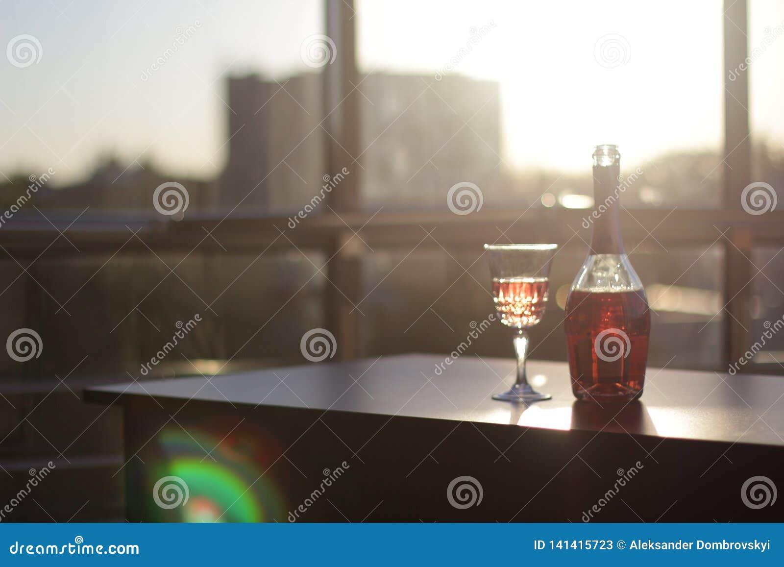 Flasche und Glas mit Wein auf dem Tisch im Büro