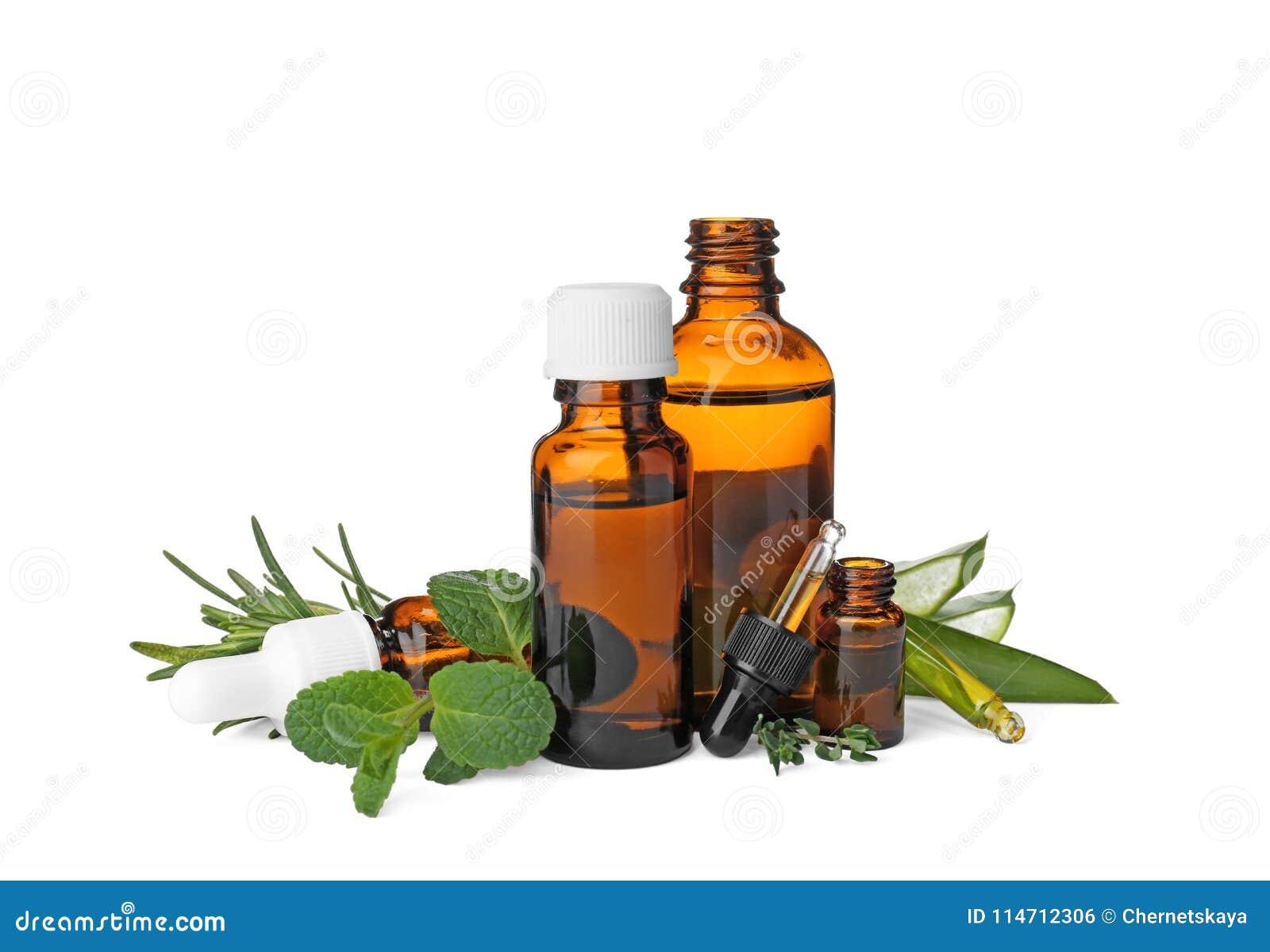 Flaschen mit ätherischen Ölen und frischen Kräutern