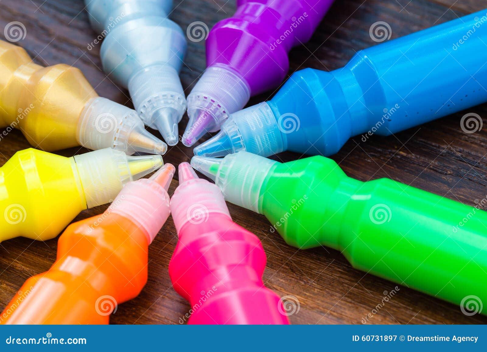 Flaschen mit bunten trockenen Pigmenten auf hölzernem Hintergrund