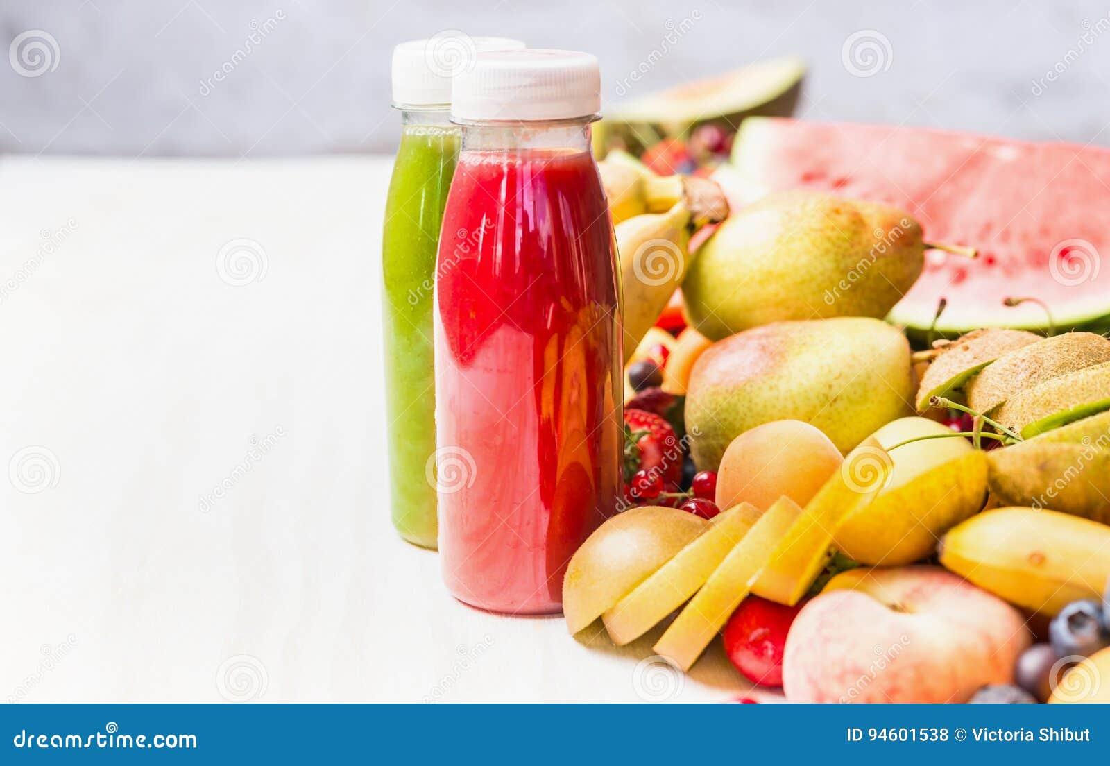 Flaschen mit roten Smoothies und Saftgetränken auf weißem Tabellenhintergrund mit Sommerfrüchten und Beeren, Vorderansicht Gesund