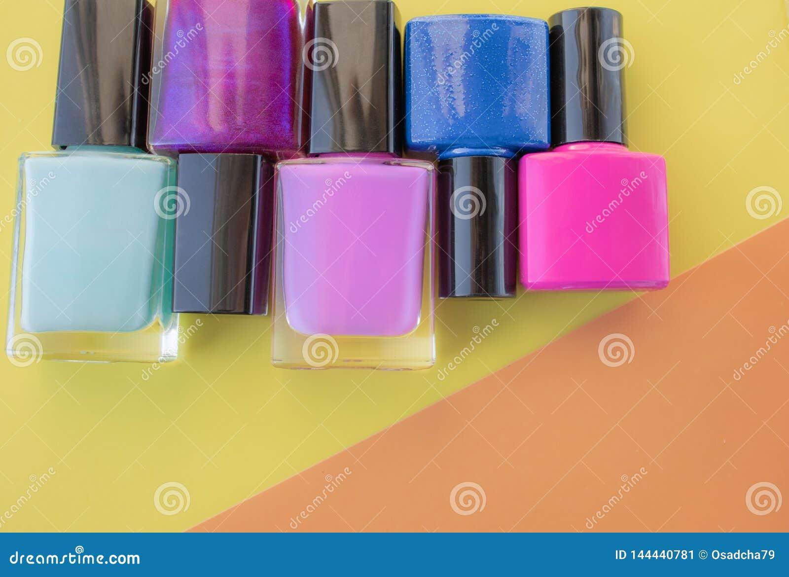 Flaschen Nagellack Eine Gruppe helle Nagellacke auf einem farbigen, gelben Hintergrund