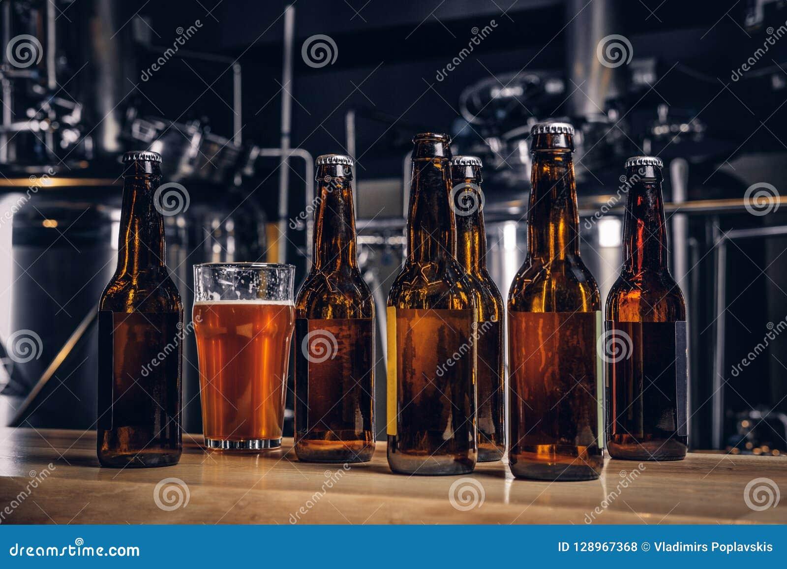 Flaschen und Glas Handwerksbier auf hölzernem Barzähler an der indie Brauerei