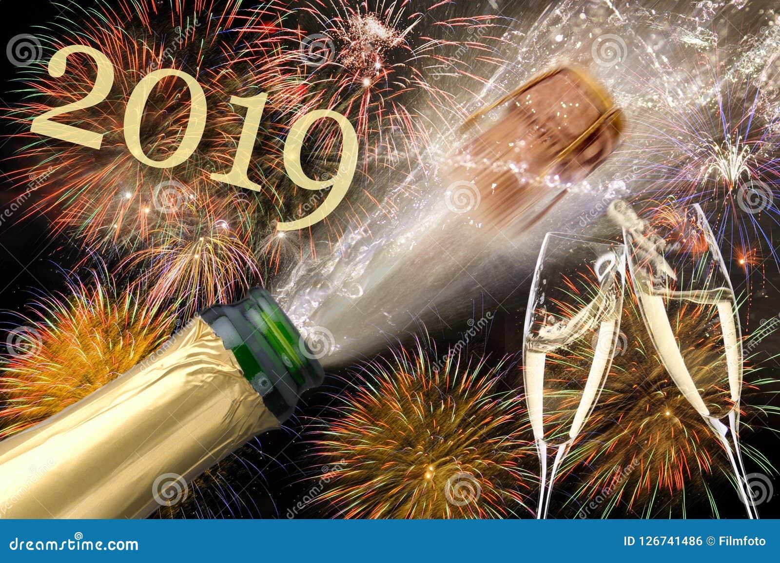 Flaska av champagne med flygkork och fyrverkerit på Silvester 2019