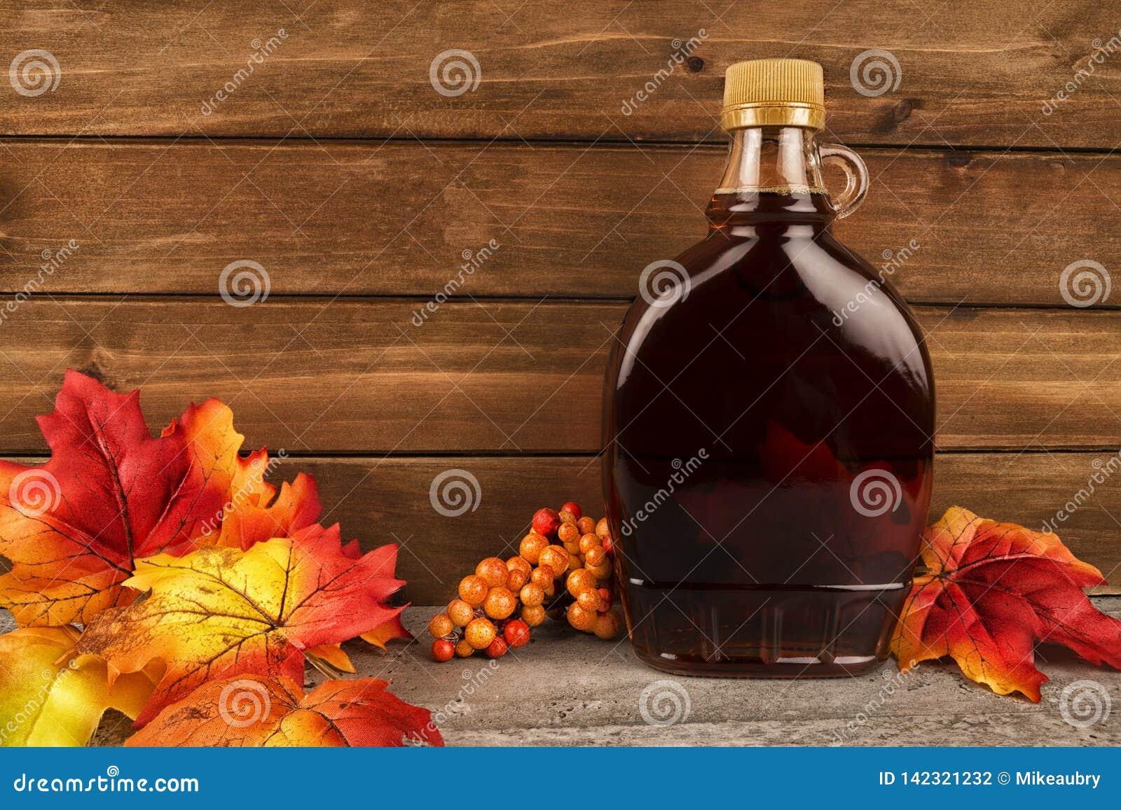 Flaska för lönnsirap på en träplankabakgrund