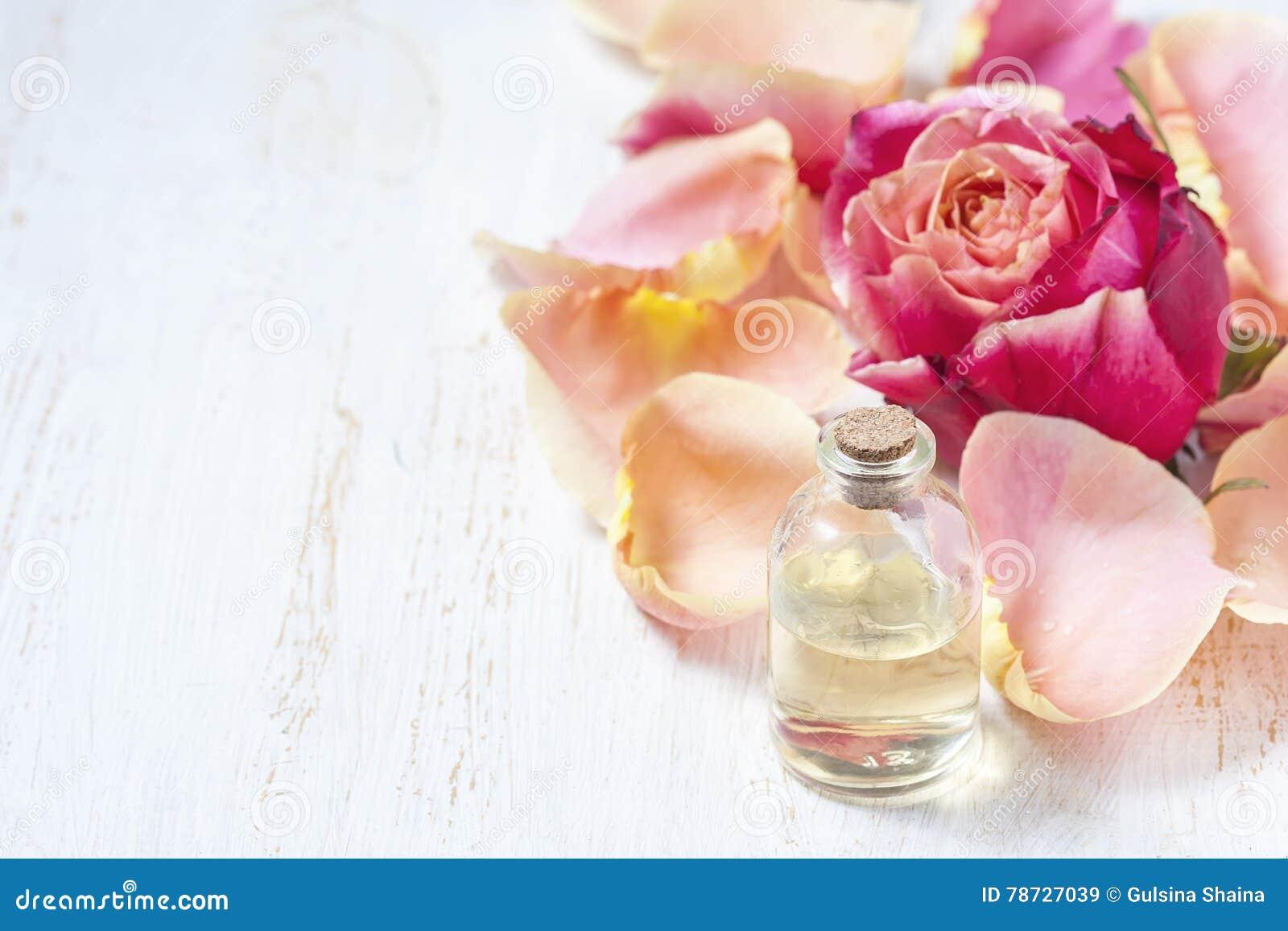 Flaska med nödvändig aromolja på vit träbakgrund