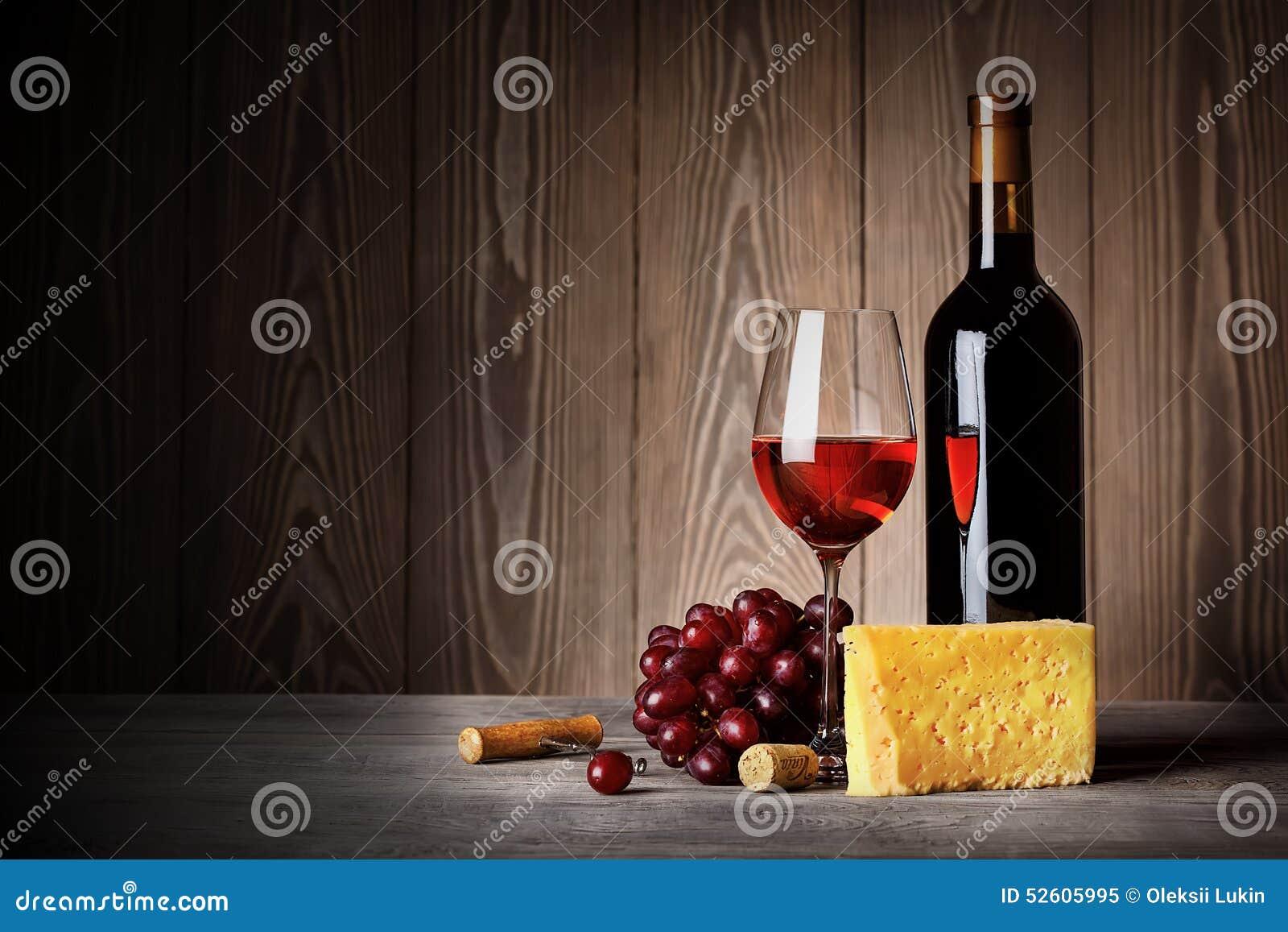 Flaska och exponeringsglas av rött vin med ostdruvor