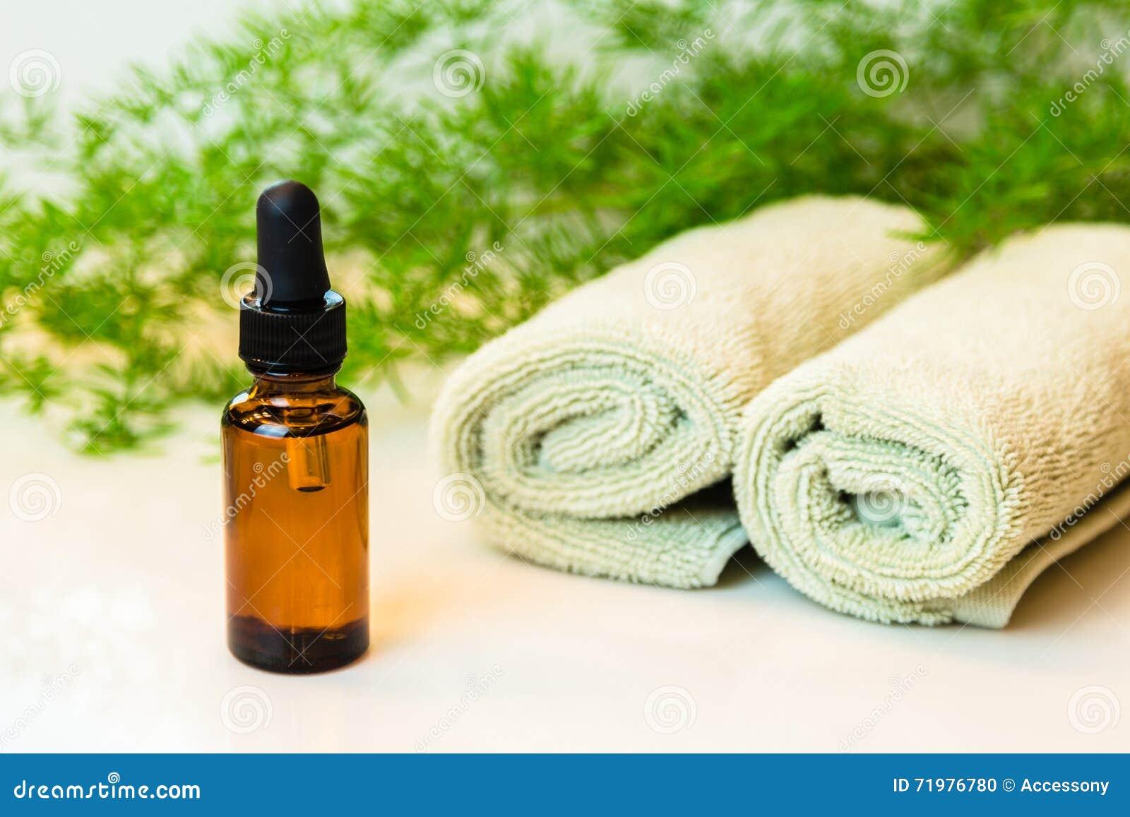 Flaskan med nödvändig olja, handdukar och gräsplaner på badrum kontrar