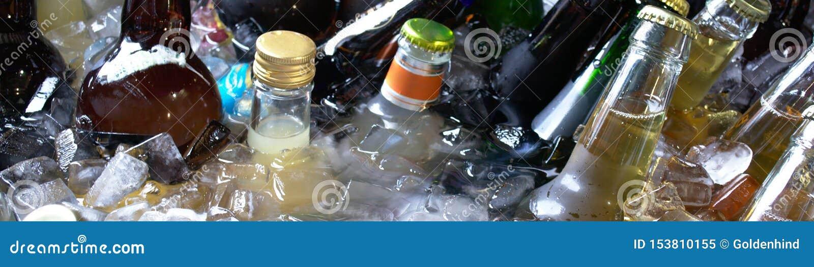 Flaskor av kalla drinkar i trumman med is i den varma sommardagen