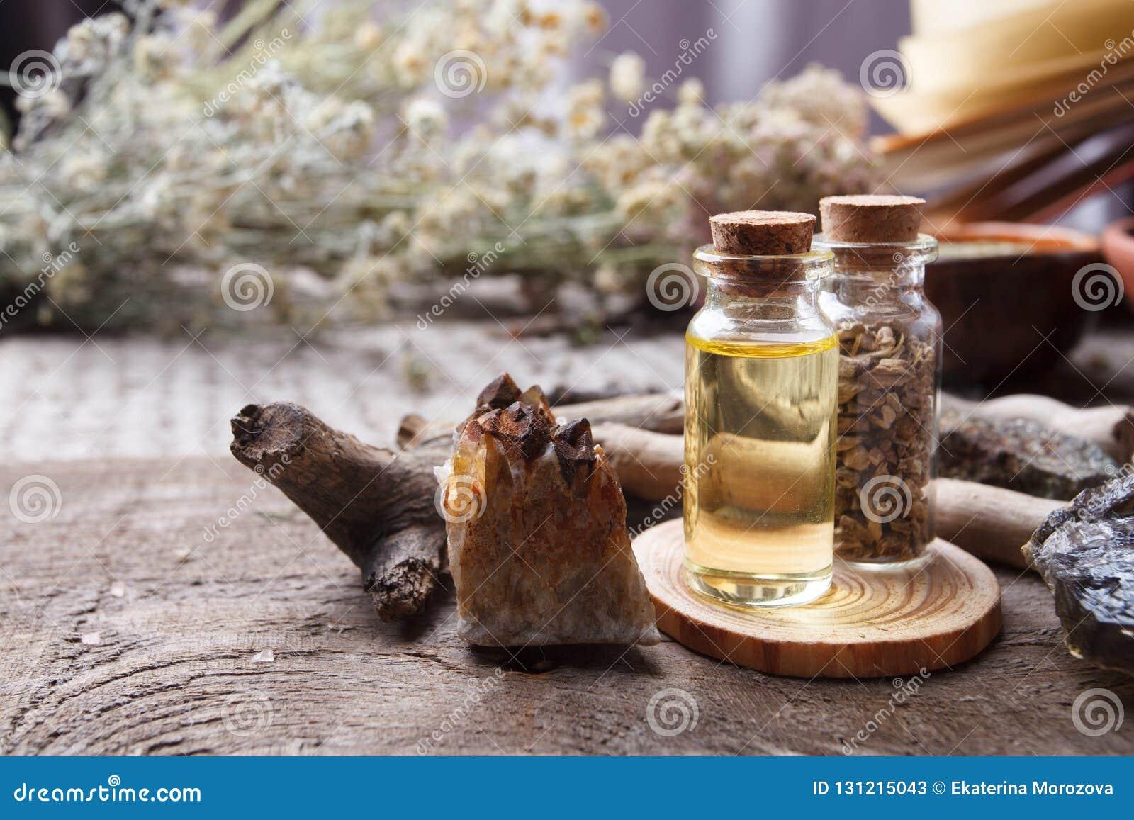 Flaskor med örter, torra blommor, stenar och magiska objekt på häxaträtabellen Ockult, esoterisk, spådom- och wiccabegrepp