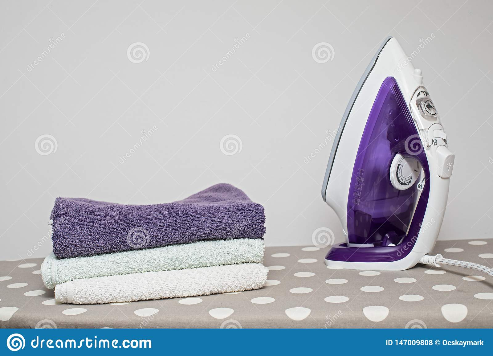 Flat iron and clean clothes on the board
