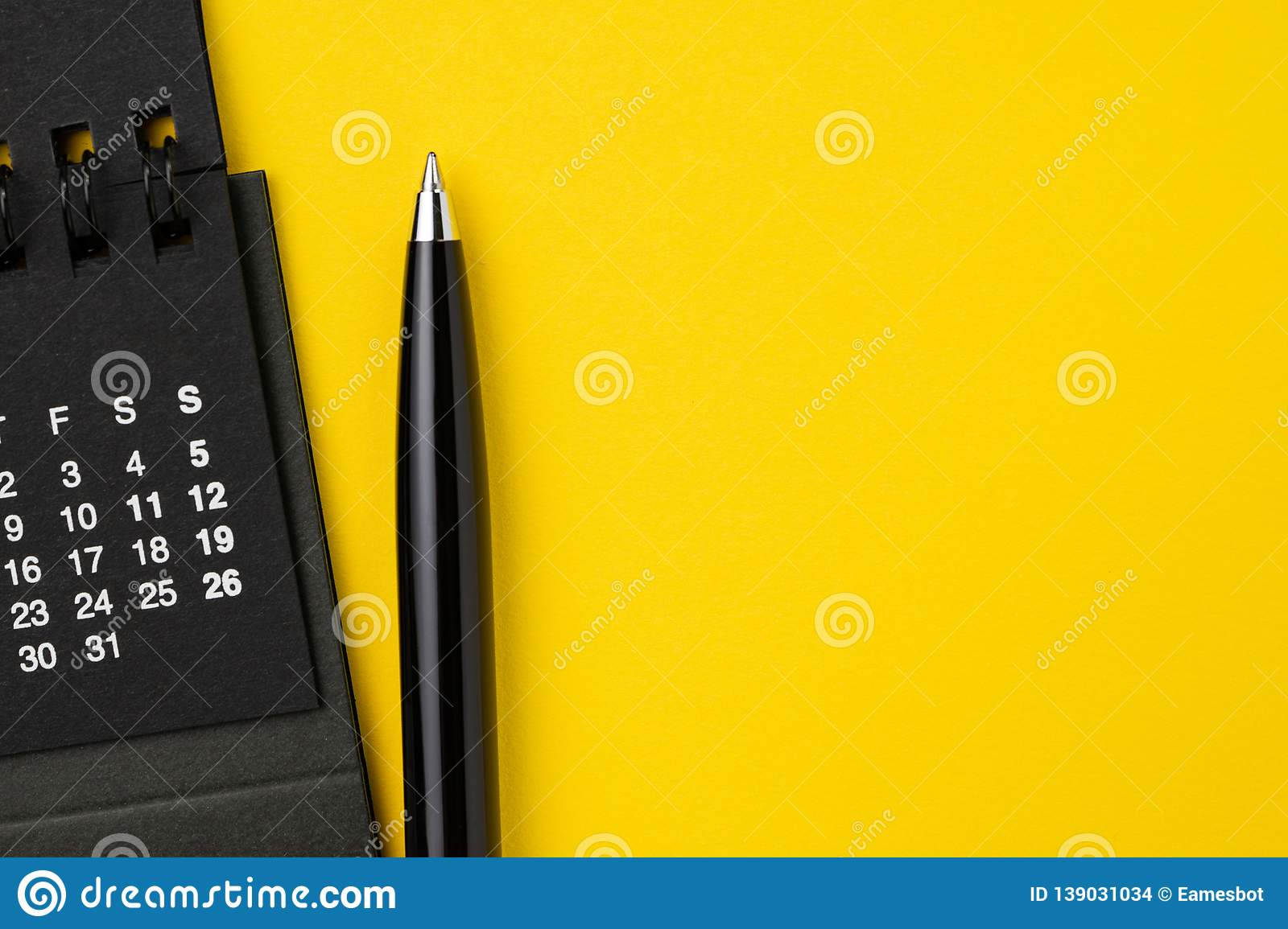 Flat lay of black calendar with white numbers with pen on solid yellow background using for business appointment, schedule and