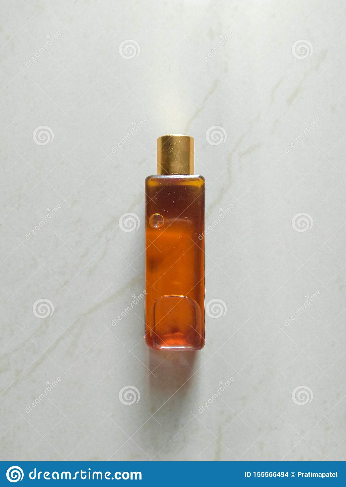 Flat lay of bottle with golden cap in white marble background