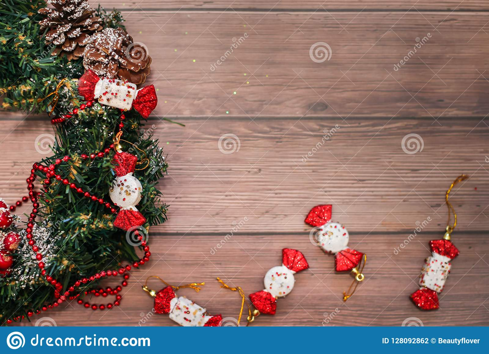 Flat lay of Christmas wreath with bumps and red decor on wooden table. Holidays christmas and new year background