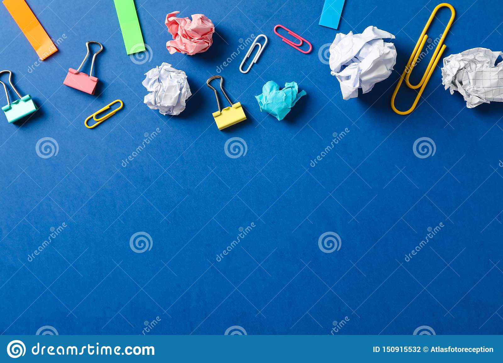 Flat lay composition with crumpled paper balls, clips and stickers on color background