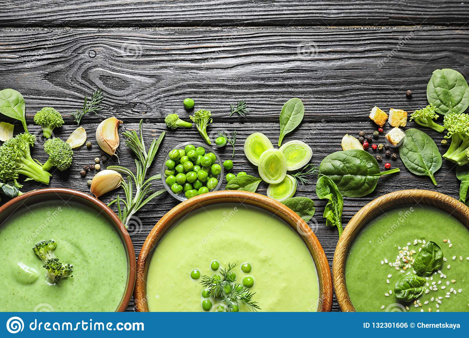 Flat lay composition with different fresh vegetable detox soups made of green peas, broccoli and spinach in dishes on table.