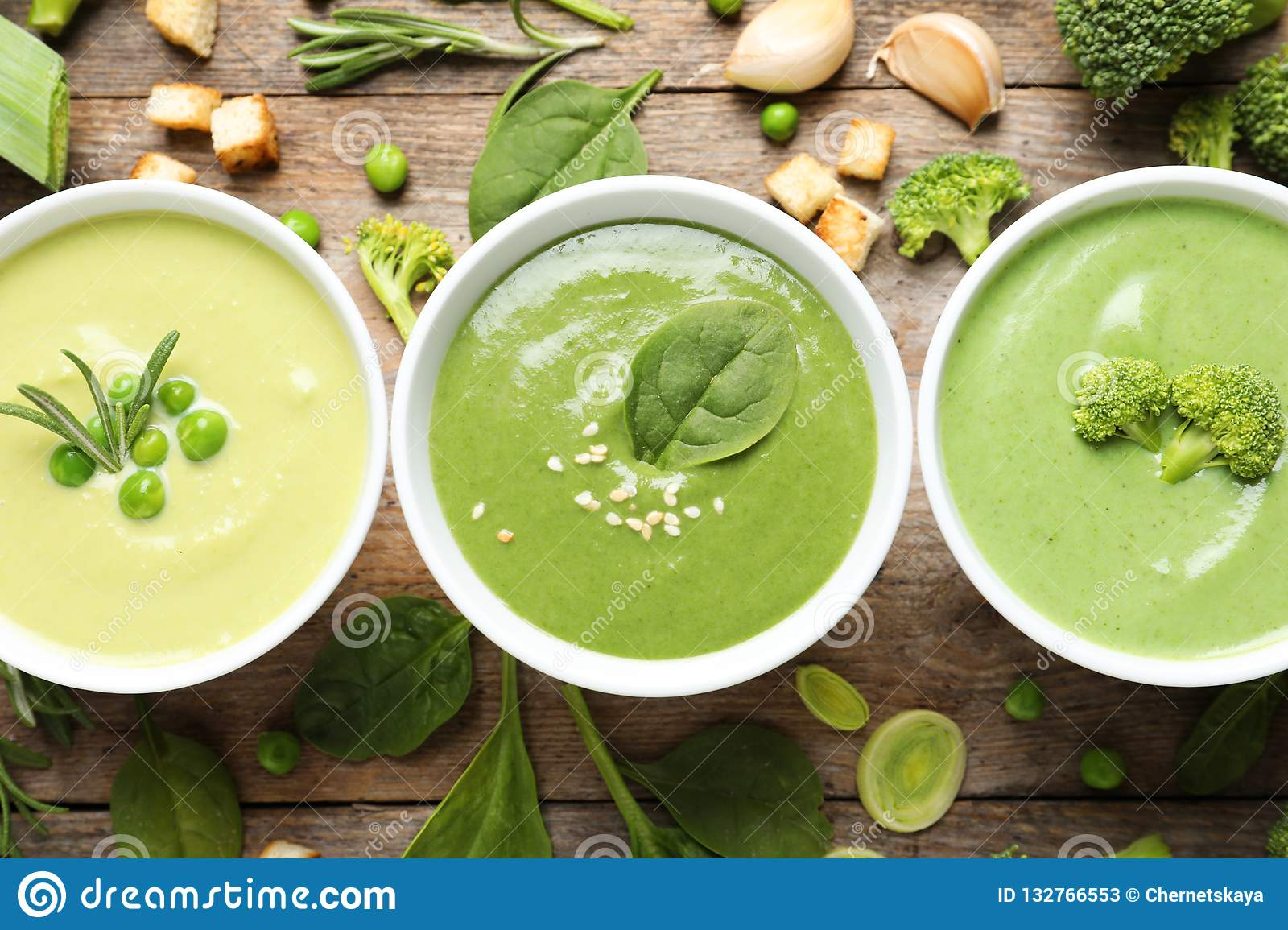 Flat lay composition with different fresh vegetable detox soups made of green peas, broccoli and spinach in dishes