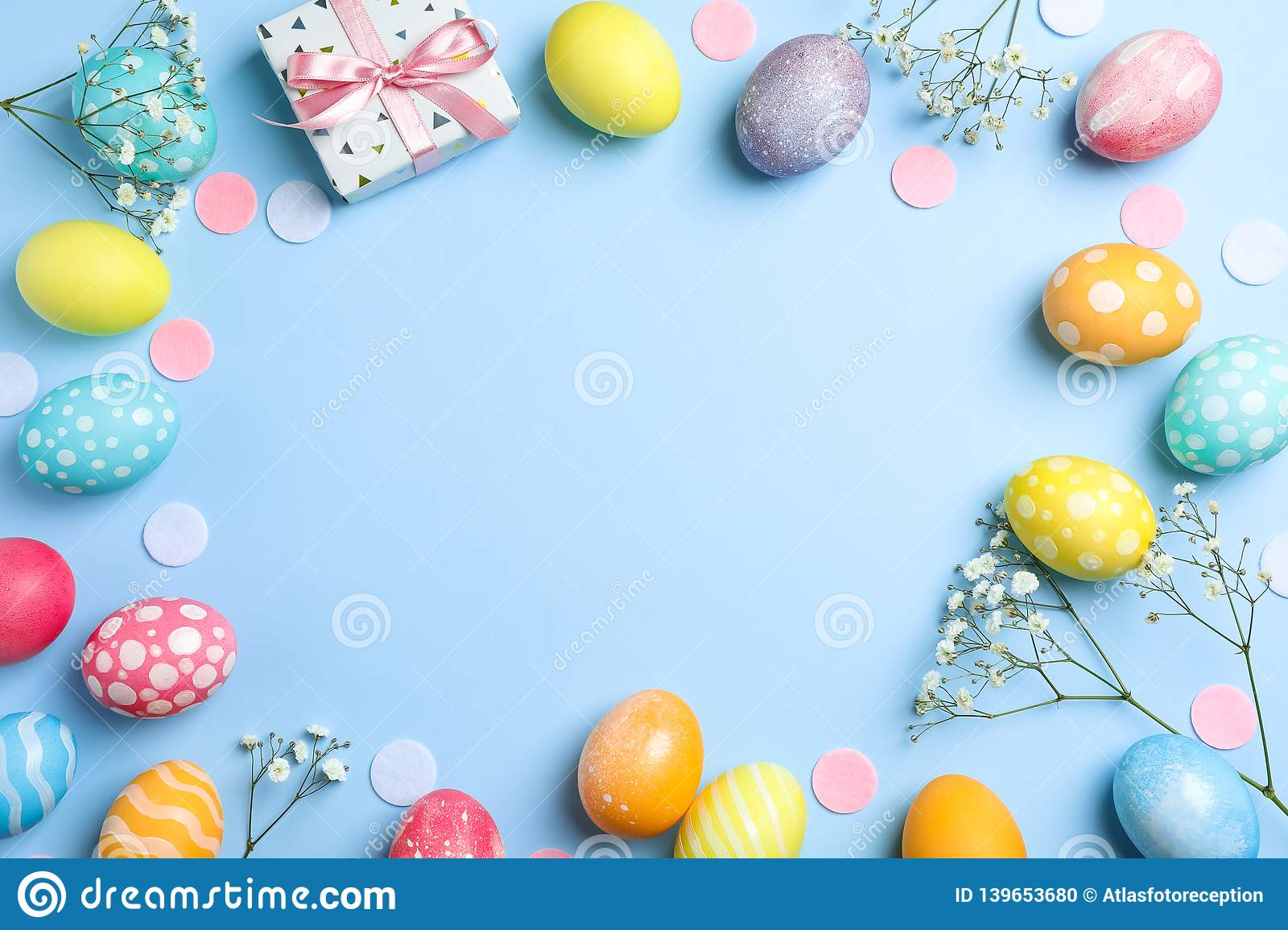 Flat lay composition with Easter eggs, present and flowers on color background, space for text