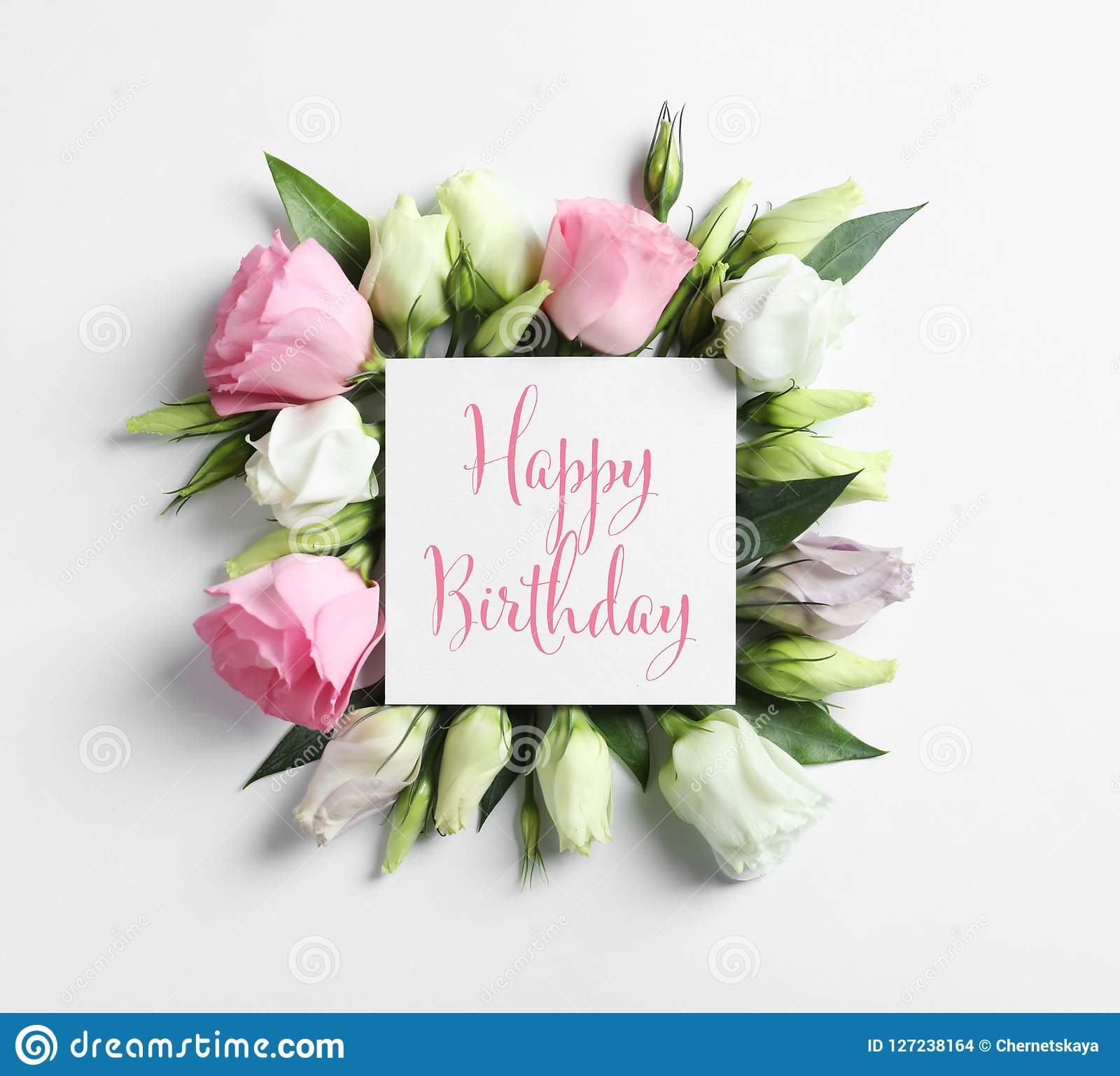 Flat lay composition of Eustoma flowers and card with greeting HAPPY BIRTHDAY