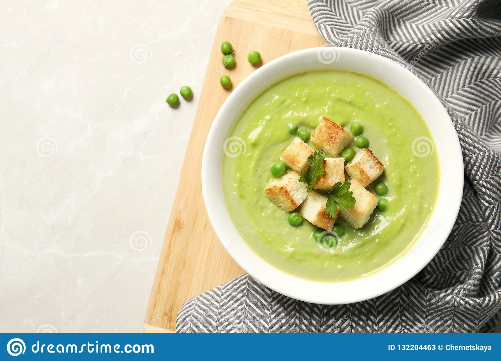 Flat lay composition with fresh vegetable detox soup made of green peas in dish and space for text