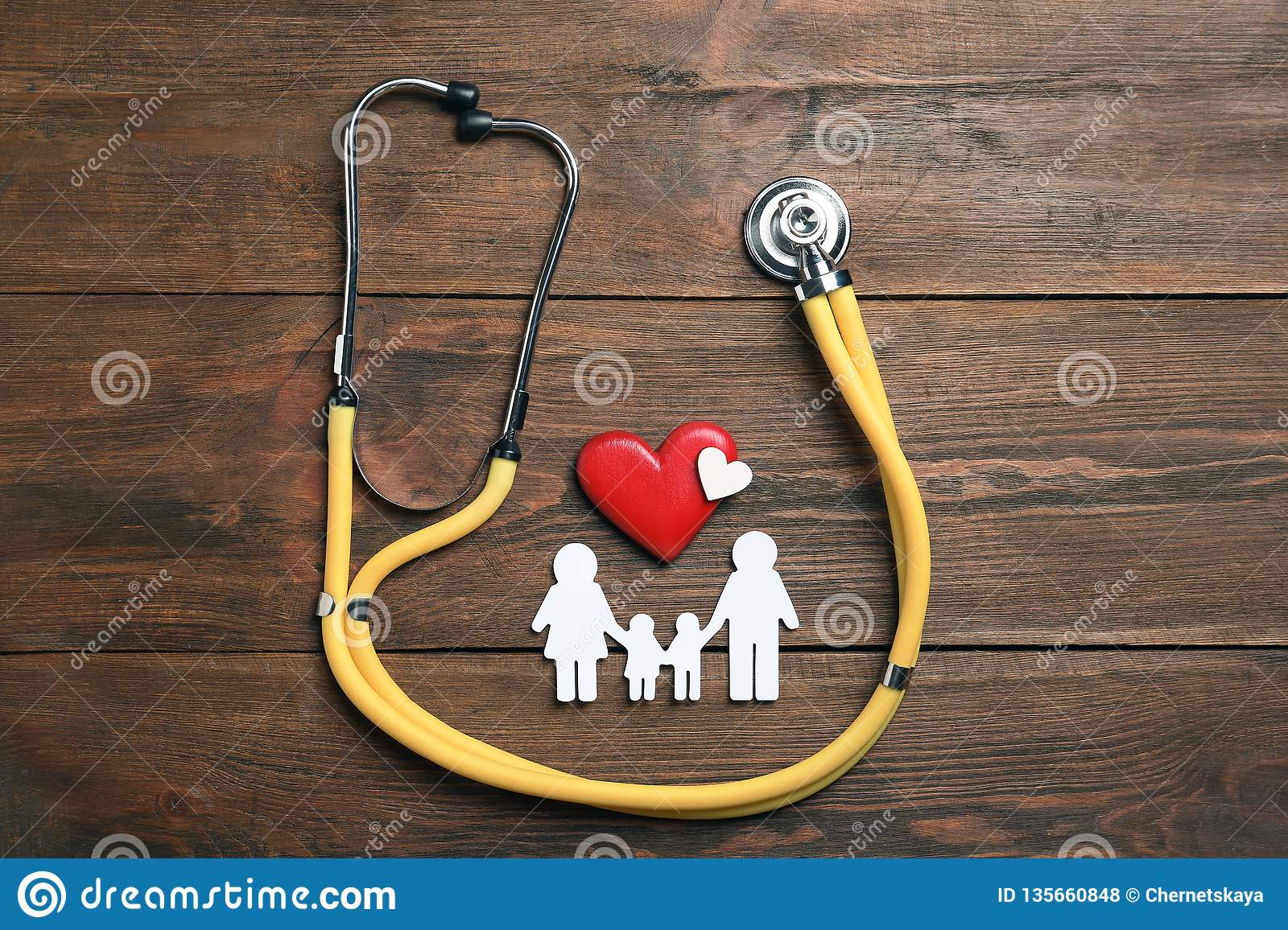 Flat lay composition with hearts, stethoscope and family silhouette on wooden background. Life insurance