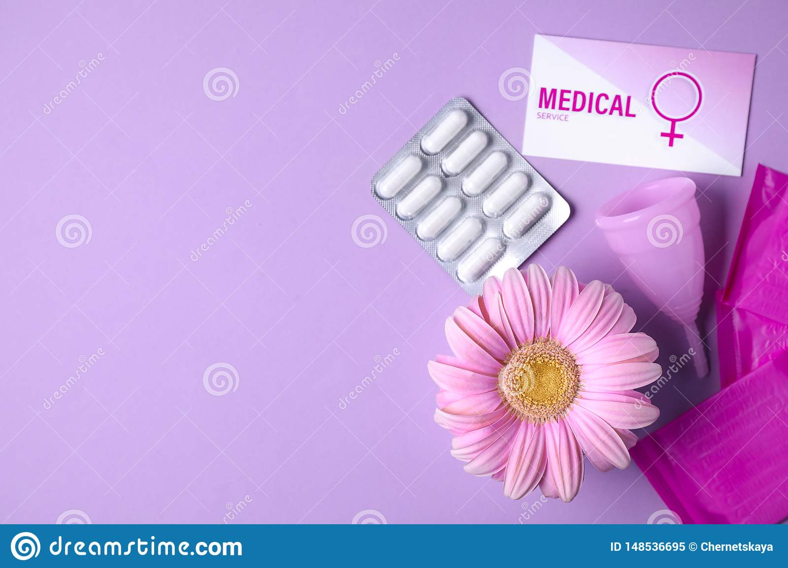 Flat lay composition with menstrual cup, pills and gerbera flower on color background, space for text.