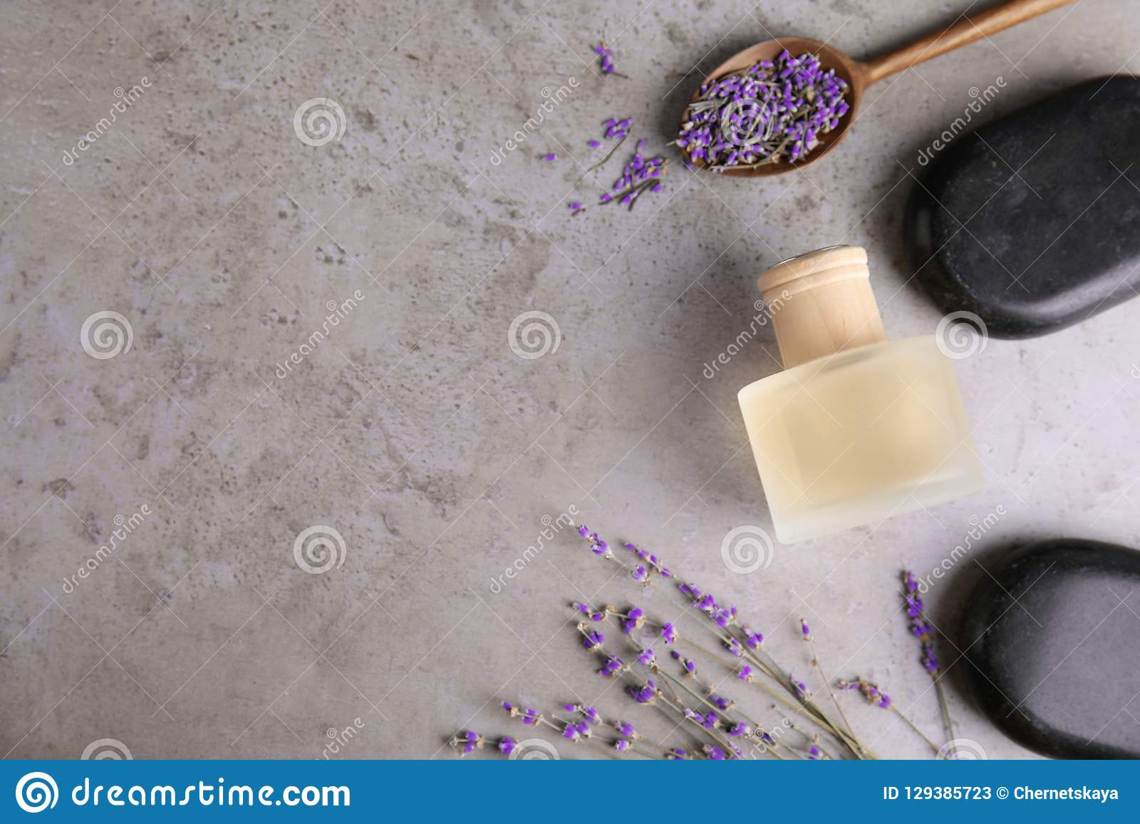 Flat lay composition with natural herbal oil and lavender flowers on color background.