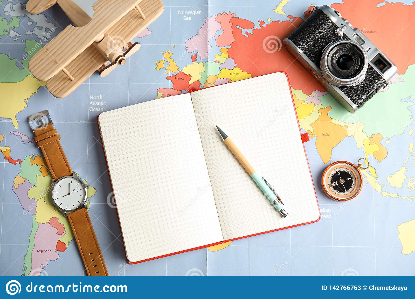 Flat lay composition with notebook and camera on world map, space for text