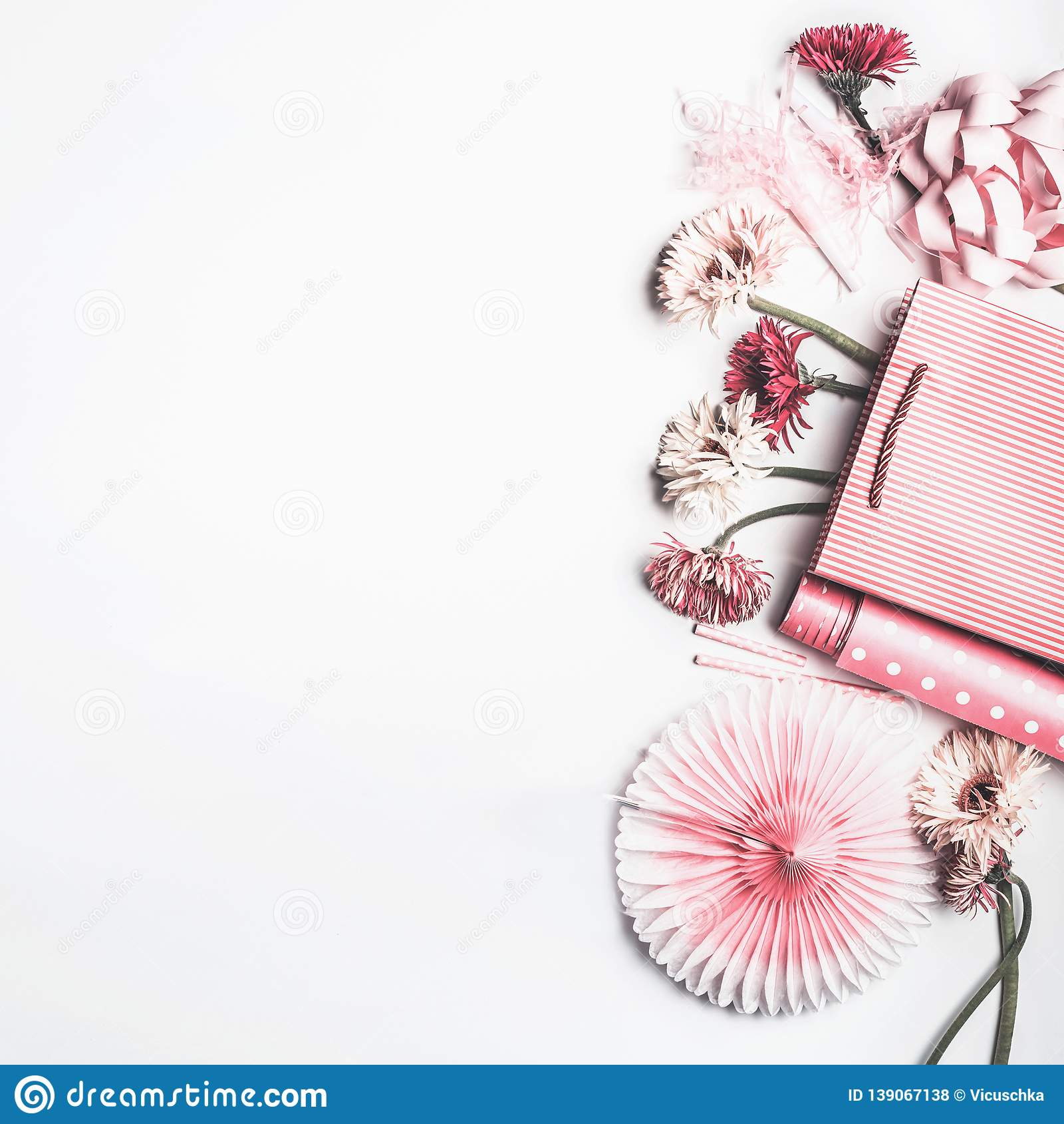 Flat lay composition of pink accessories to female holidays: Mothers day , Womens day, birthday. Paper shopping bag with flowers,