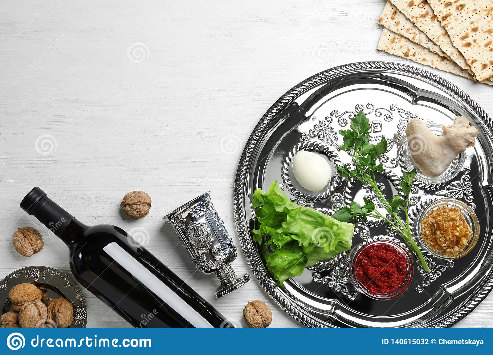Flat lay composition with symbolic Passover Pesach items and meal on wooden background