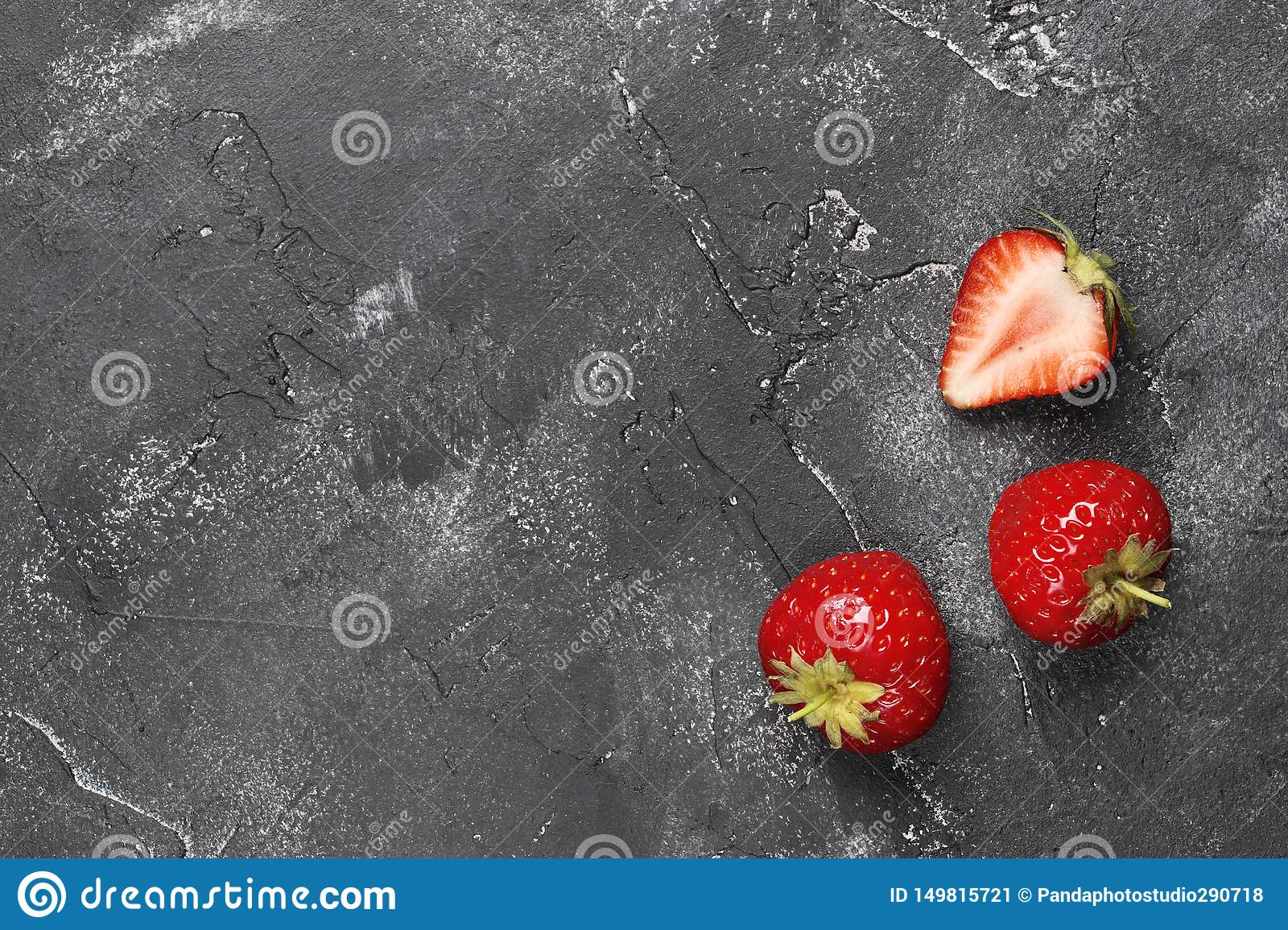Flat lay composition of three ripe strawberries on a dark background